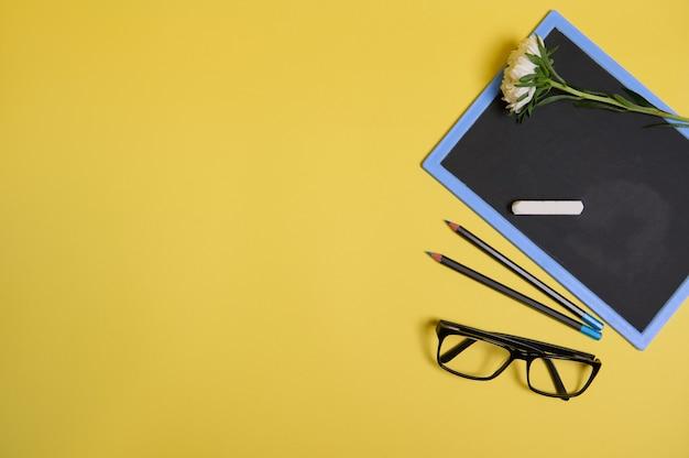 Vista dall'alto. disposizione piatta. fiore di aster d'autunno su una lavagna pulita con spazio per copia, occhiali e due matite, isolato su sfondo giallo con spazio per il testo