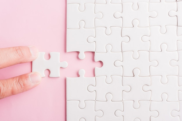 Vista dall'alto piatto della disposizione dell'ultimo pezzo di carta bianca del gioco di puzzle degli ultimi pezzi messi a posto per risolvere il problema completa la missione