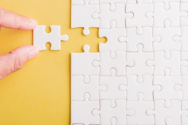 Vista dall'alto posa piatta della presa dell'ultimo pezzo di carta bianca gioco di puzzle ultimi pezzi messi a posto