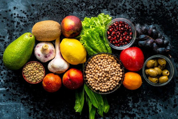 Vista dall'alto distesa piatta di una selezione di cibi sani con semi di frutta verdura ed erbe verdi sui tavoli