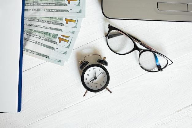 Vista dall'alto piatta del posto di lavoro moderno di laptop, orologio, denaro, banconote in dollari con spazio per copia su fondo di legno bianco. tempo per soldi.