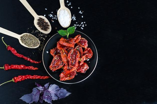 Vista dall'alto, piatto di processo di cottura dei pomodori secchi nella ciotola, ingredienti e spezie per uno spuntino su sfondo nero con copia spazio, posto per il testo.