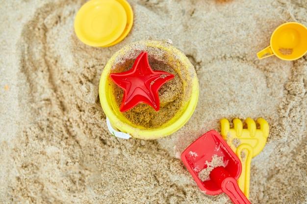 Vista dall'alto, disposizione piatta di giocattoli da spiaggia di plastica sparsi su sfondo di sabbia, vacanze estive in famiglia