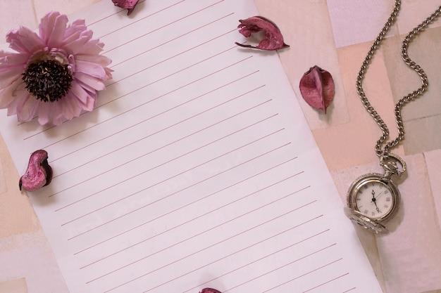 Vista dall'alto colpo piatto laici di busta di carta da lettere e orologio da tasca con petali di fiori