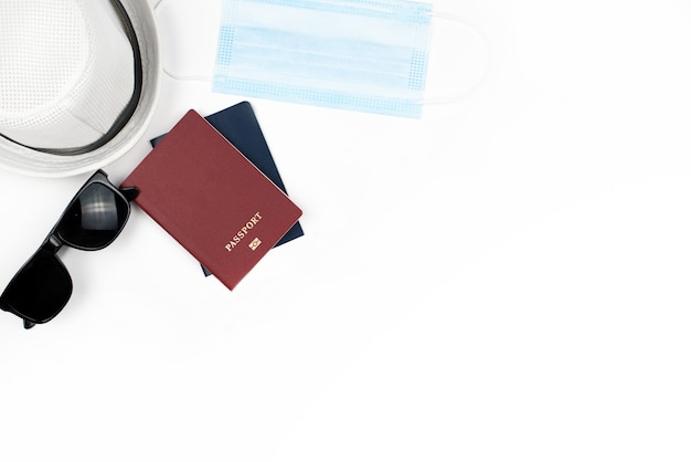Vista dall'alto o disposizione piatta degli accessori da viaggio con maschera igienica e passaporto sul tavolo bianco blu con spazio di copia, protezione contro il virus corona o covid-19 durante il viaggio.