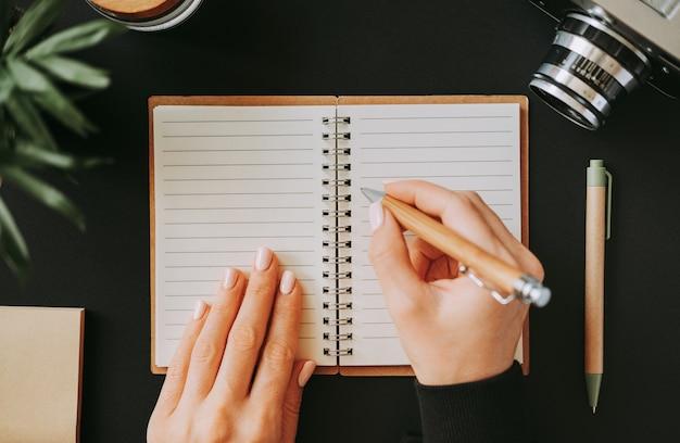 Vista dall'alto del piatto laici mano della donna scrive gli indirizzi in un taccuino aperto che giace sulla tavola nera accanto alla fotocamera con penna e blocco note