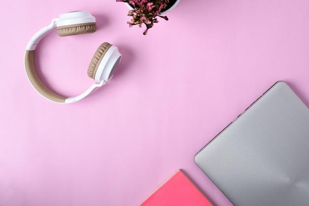 Vista dall'alto flatlay di moderne cuffie wireless, laptop minimalista, simpatico fiore viola e libro su area di lavoro di colore rosa