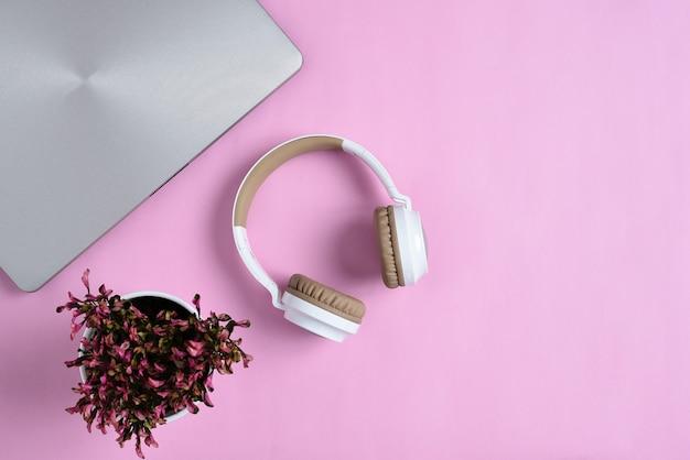 Vista dall'alto flatlay di moderne cuffie wireless, laptop minimalista e simpatico fiore viola su area di lavoro di colore rosa
