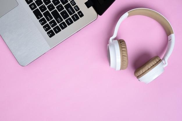 Vista dall'alto flatlay di moderne cuffie wireless e laptop minimalista su area di lavoro di colore rosa