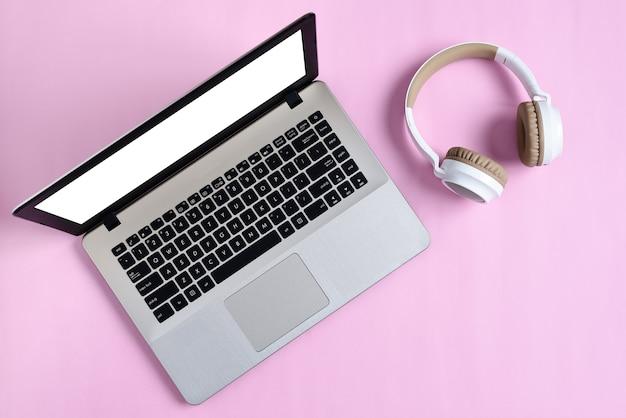 Vista dall'alto flatlay di moderne cuffie wireless e laptop minimalista con schermo bianco su area di lavoro di colore rosa