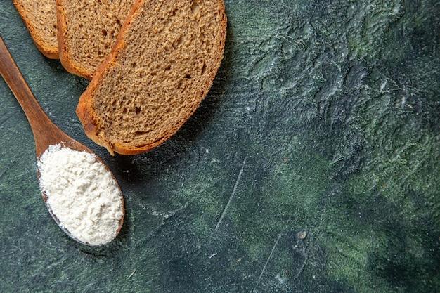 Farina vista dall'alto sul cucchiaio di legno con pagnotte di pane scuro sulla scrivania scura
