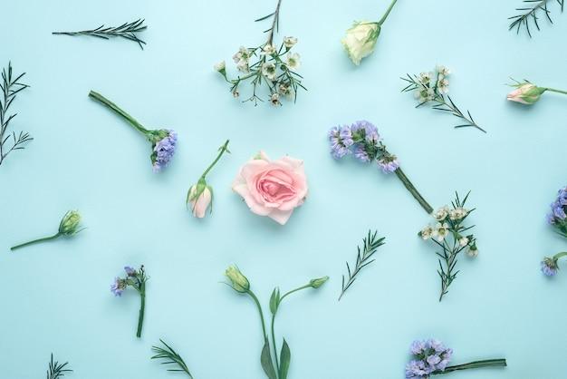 Composizione floreale vista dall'alto, infiorescenze rosa, eustoma, limonium su sfondo blu, piatto laici