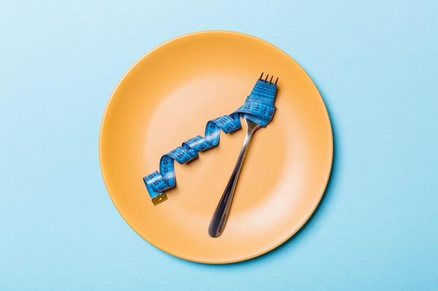 Vista superiore della forcella con nastro adesivo di misura nel piatto rotondo su sfondo blu. concetto di perdita di peso con spazio vuoto per la tua idea