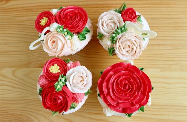 Vista dall'alto di quattro cupcakes con splendida glassa a forma di fiore rosso e rosa