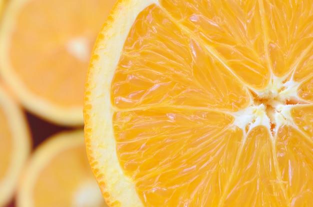 Vista dall'alto di un frammento della fetta di frutta arancione sullo sfondo di molte fette di arancia offuscata. un'immagine di trama di agrumi saturi