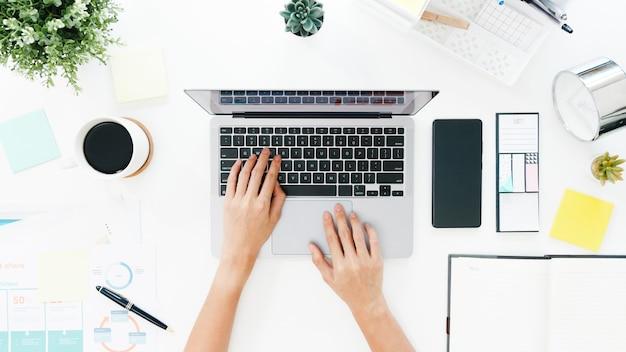Vista dall'alto della signora asiatica freelance utilizzando il computer portatile nel soggiorno di casa