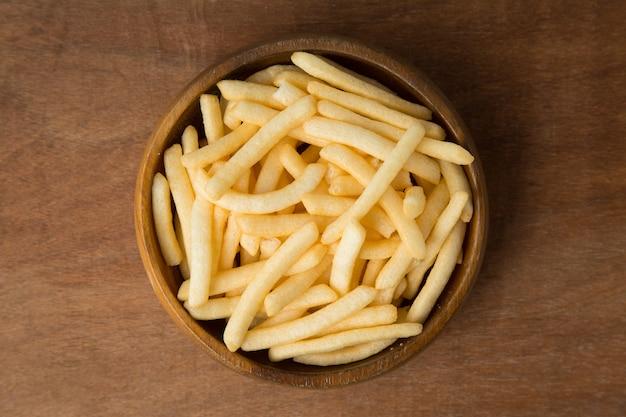 La vista superiore delle patate fritte o della patata frigge in ciotola di legno che mette su fondo di legno e di tela.