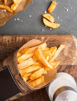 Vista dall'alto di patatine fritte con saliera