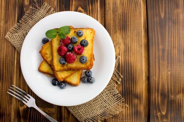 Vista dall'alto di toast francesi con frutti di bosco e miele nel piatto bianco sulla superficie rustica
