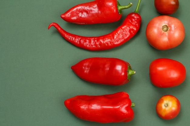 Vista dall'alto di peperoni freschi, peperoncino rosso e pomodori su sfondo verde. frutta e verdura sul tavolo della cucina.