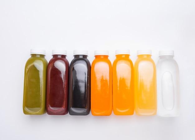 Vista dall'alto di bottiglie di succo di disintossicazione fresca su bianco. stile sano