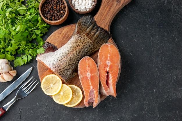 Vista dall'alto pesce fresco con fettine di limone su sfondo scuro insalata oceano pasto a base di pesce cibo pasto acqua pesce di mare carne