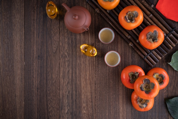 Vista dall'alto di cachi freschi sul fondo della tavola in legno per il nuovo anno lunare cinese