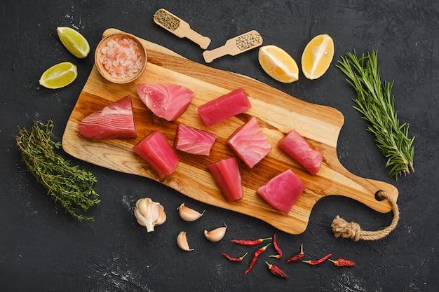 Vista dall'alto di pezzi freschi di filetto di tonno con spezie ed erbe aromatiche sul tagliere di legno