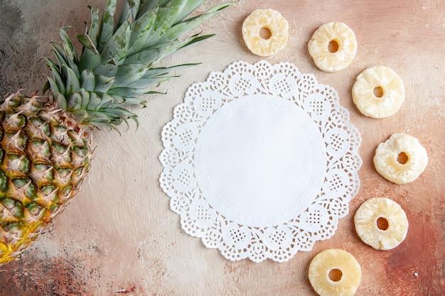 Vista dall'alto ananas fresco ananas secco anelli centrino di pizzo bianco su sfondo beige