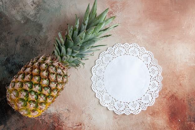 Vista dall'alto centrino di pizzo bianco ananas fresco su sfondo beige