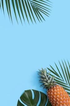 Vista dall'alto di ananas fresco con palme tropicali e foglie di monstera sul fondo della tavola blu.