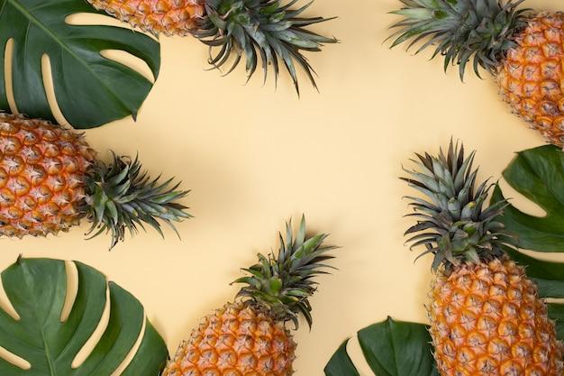 Vista dall'alto di ananas fresco con palme tropicali e foglie di monstera sul fondo della tavola gialla.