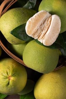 Vista dall'alto di pomelo fresco su sfondo tavolo in legno scuro per frutta mid-autumn festival.