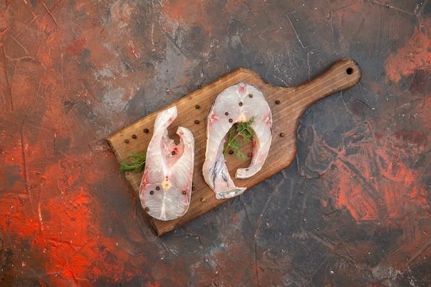 Vista dall'alto di pesce crudo fresco e pepe sul tagliere di legno sulla superficie di colore della miscela