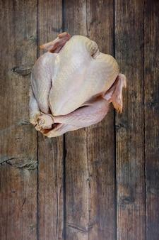 Vista dall'alto di intero tacchino crudo fresco su fondo di legno. piatto del ringraziamento.