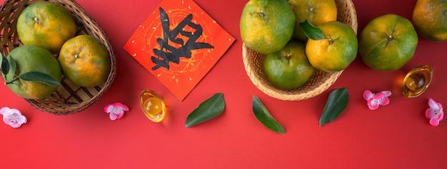 Vista dall'alto del mandarino mandarino maturo fresco con foglie fresche sul fondo della tavola rossa per il concetto di frutta del nuovo anno lunare cinese, la parola cinese significa primavera.