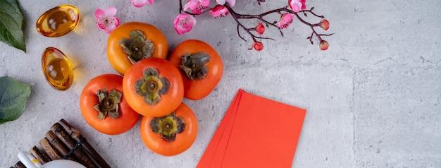 Vista dall'alto di kaki cachi dolce fresco con foglie sul tavolo grigio per il concetto di capodanno lunare cinese, la parola significa che la primavera sta arrivando.