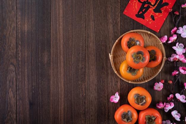 Vista dall'alto di kaki cachi dolce fresco con foglie sul fondo della tavola in legno
