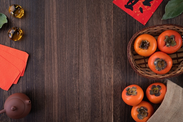 Vista dall'alto di kaki dolce fresco di cachi con foglie sul tavolo di legno per il concetto di capodanno lunare cinese, la parola significa che la benedizione sta arrivando.