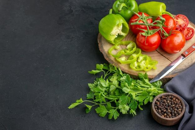 Vista dall'alto di pomodori freschi e peperoni verdi sul fascio di bordo di legno verde sul lato sinistro sulla superficie nera