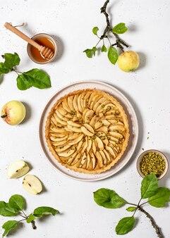 Vista dall'alto della torta di mele appena sfornata con ripieno di crema pasticcera e pistacchi verdi