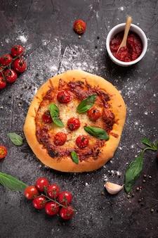 Vista dall'alto della pizza appena sfornata con formaggio, pomodori e basilico