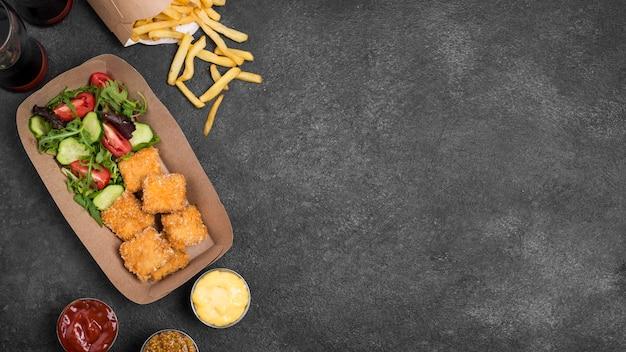 Vista dall'alto di pepite di pollo fritto con copia spazio e patatine fritte