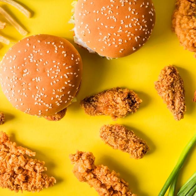 Vista dall'alto ali di pollo fritte e hamburger con patatine fritte