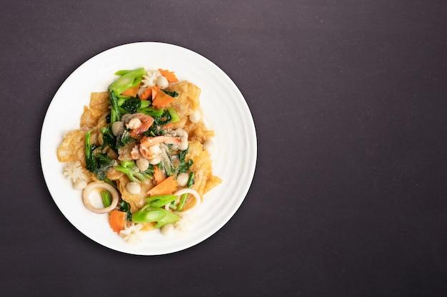 Vista dall'alto. tagliatella fritta con frutti di mare e verdura nel piatto rotondo bianco isolato su priorità bassa nera. concetto di cibo tailandese