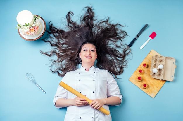 Vista dall'alto della donna pasticcere pasticcere panettiere con lunghi capelli scuri intorno torta di compleanno di nozze, uova di biscotti, frusta e mattarello sdraiato sul pavimento in studio su sfondo blu.