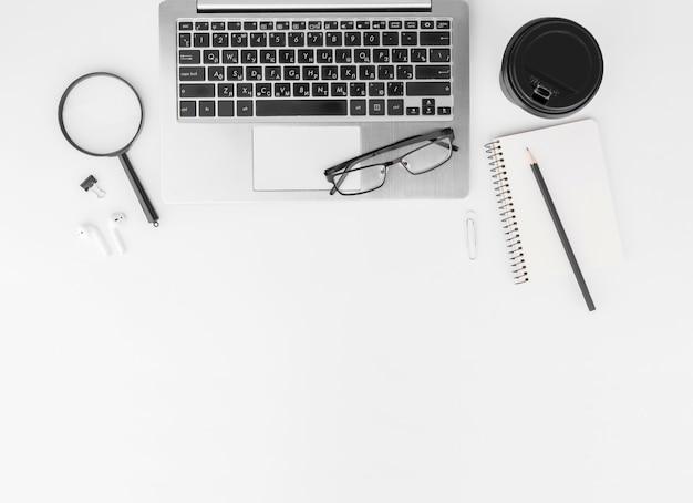Vista dall'alto dall'alto della tastiera con taccuino, matita, occhiali da vista e caffè