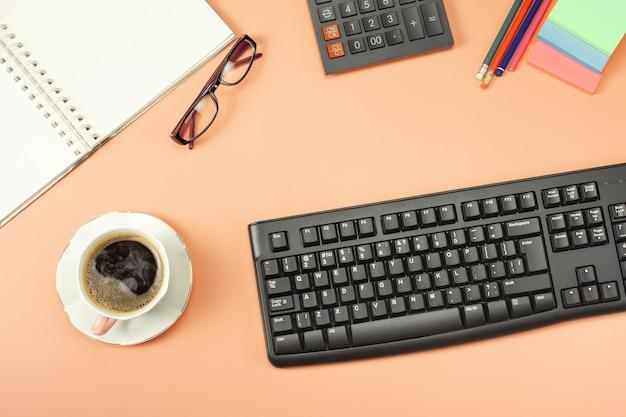 Vista dall'alto dall'alto della tastiera con blocco note e caffè. lay piatto con copia spazio vuoto. finanza o background aziendale