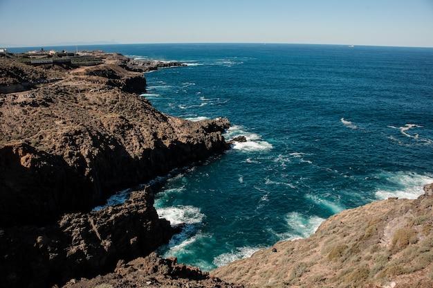 Vista dall'alto da una montagna di un mare profondo e luminoso con onde sotto il cielo blu chiaro in giornata di sole