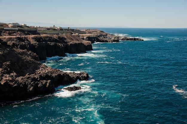 Vista dall'alto da una montagna con una piccola città di un mare profondo e luminoso con onde sotto il cielo blu chiaro in giornata di sole